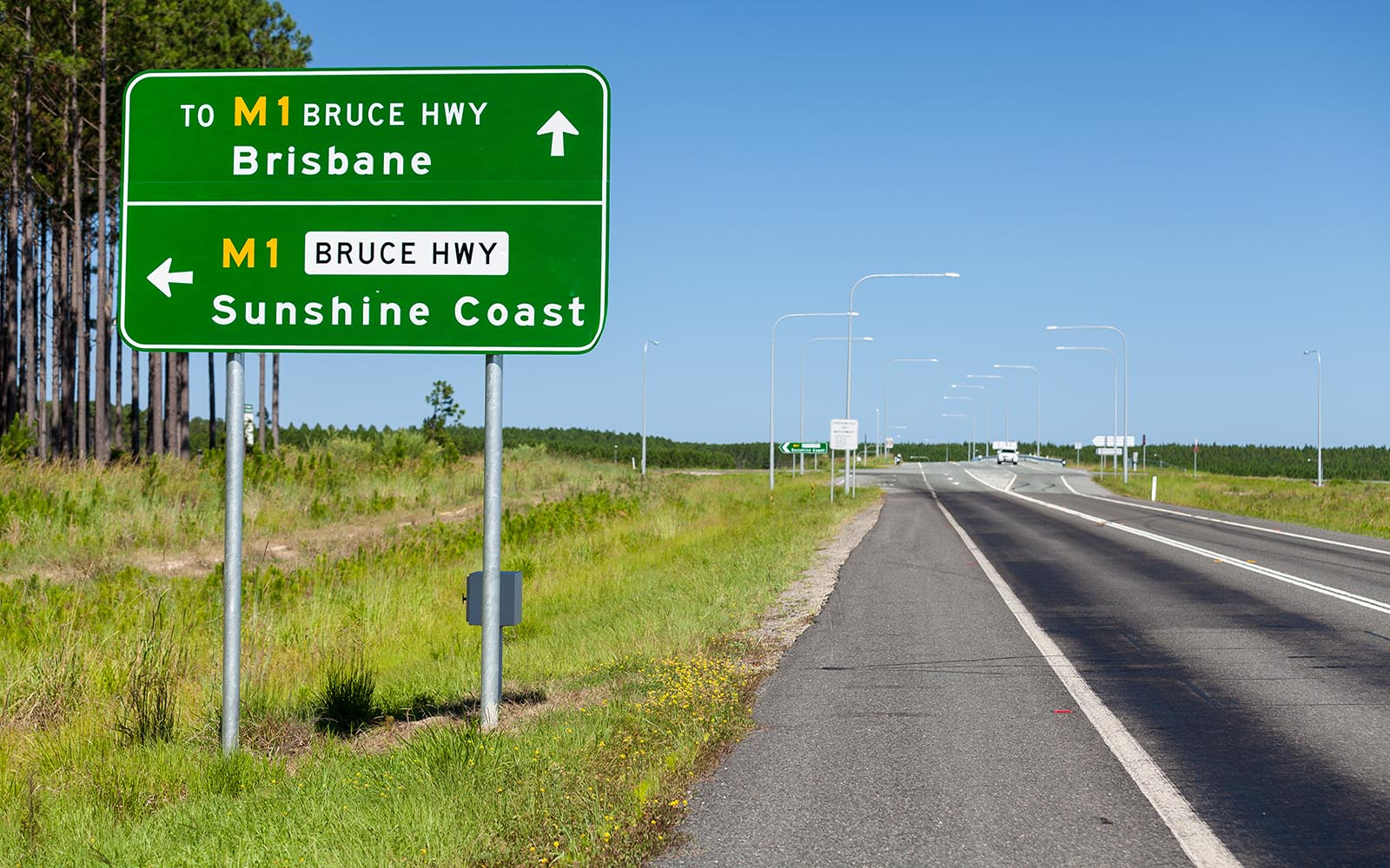 Bruce Highway road sign positioned next to empty motorway in Queensland Australia
