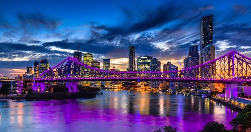Story Bridge at night with purple lights reflected onto river in Brisbane Australia