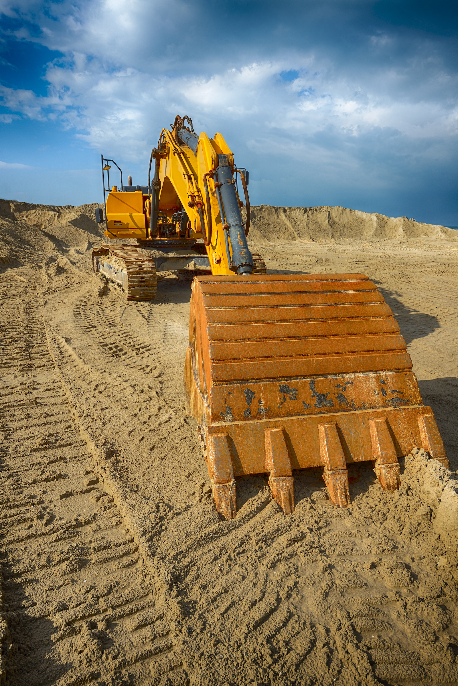 Digger on sand bank being used for environmental investigation and remediation