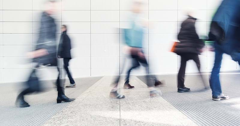 Businesspeople walking quickly in an urban environment