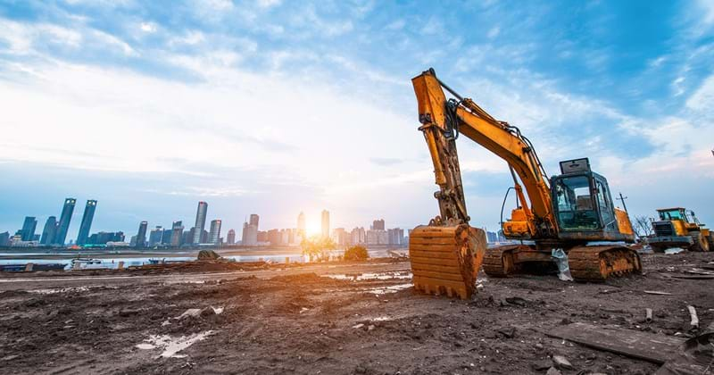 Excavators working on contaminated urban waterfront land with cityscape in background