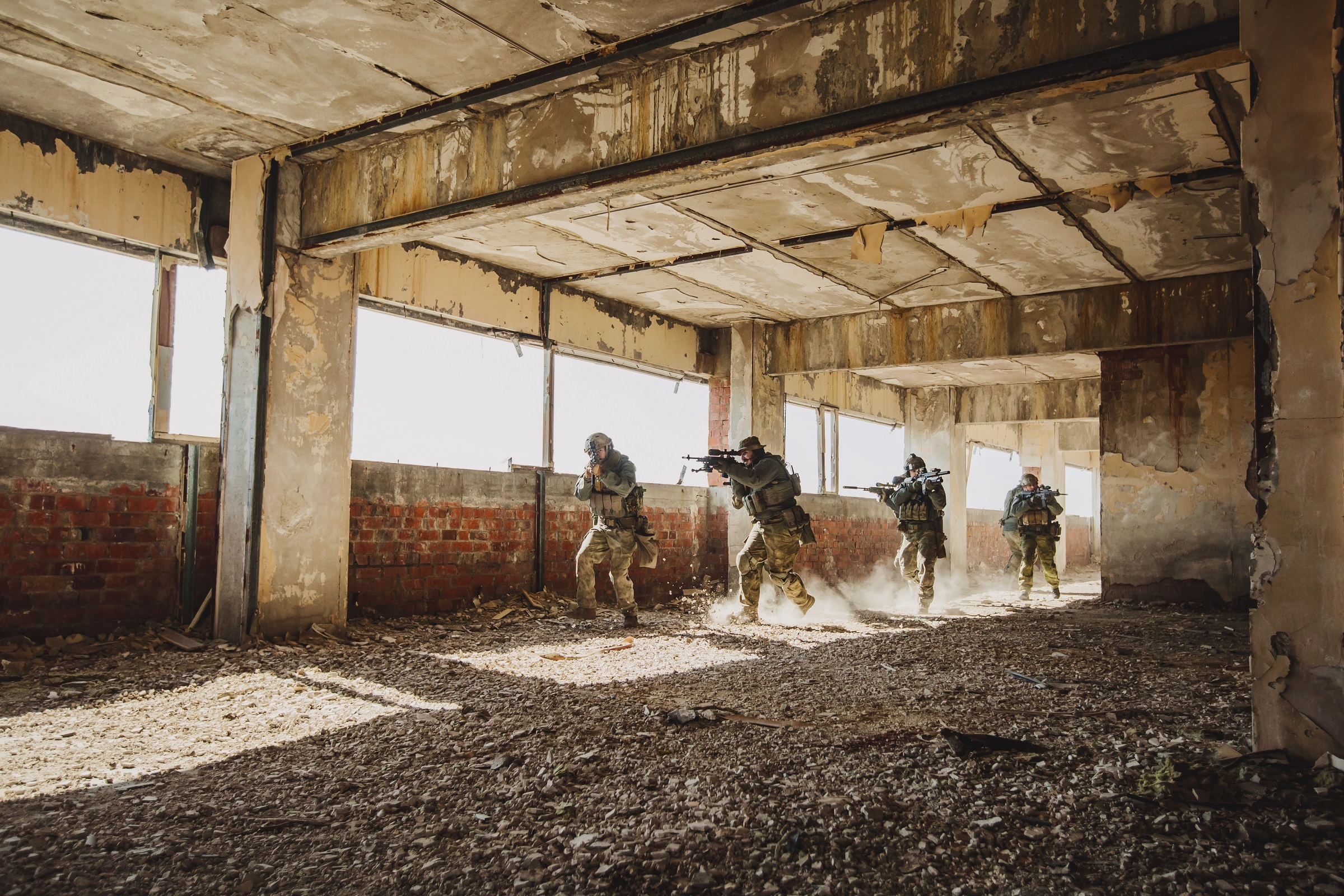 Soldiers in training completing a group manoeuvre to simulate an urban combat scenario