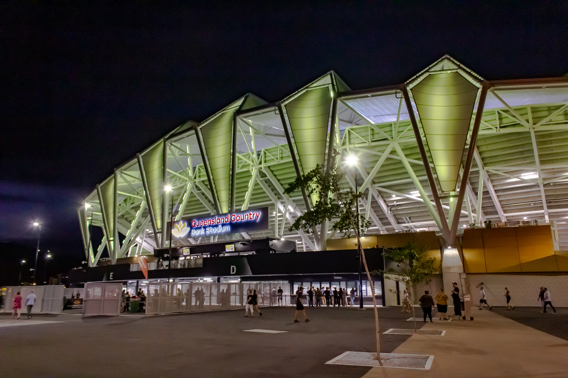 People walking past Queensland Country Bank Stadium in Townsville in the evening