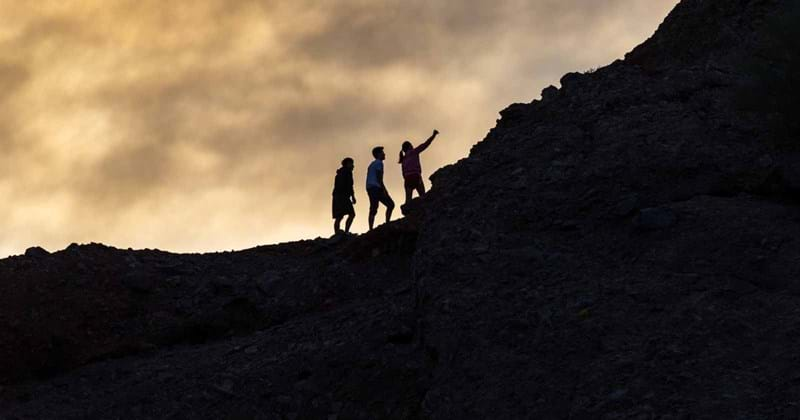 Three people climbing a hill