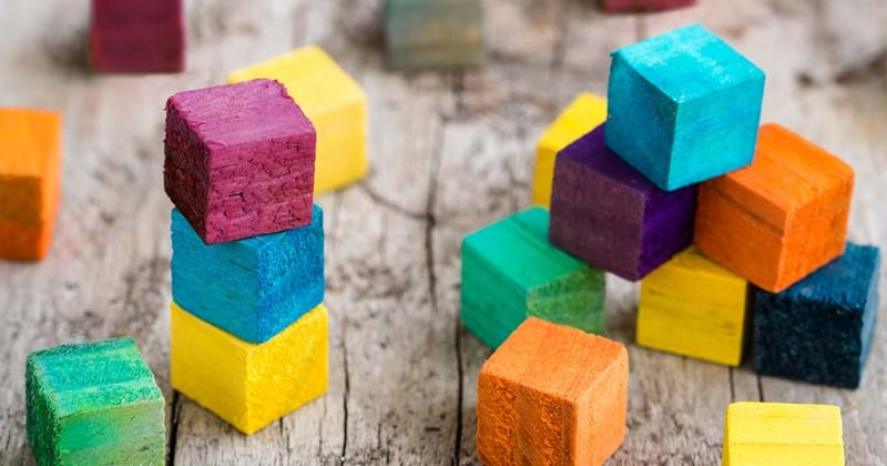 Wooden stacked coloured blocks building blocks representing fast tracked infrastructure