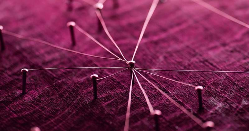 Pins in plum coloured board representing a network for fast tracked infrastructure